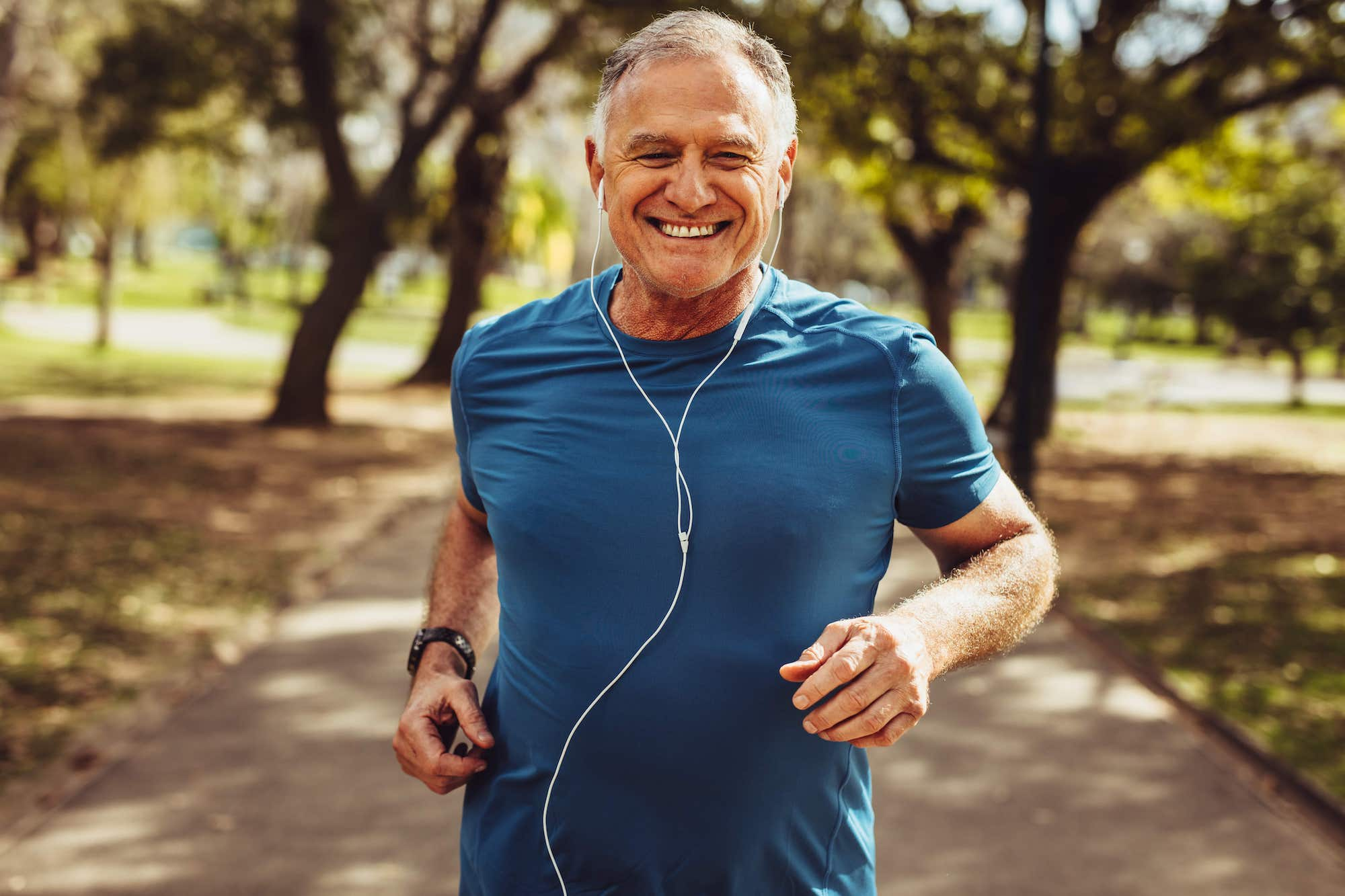 An elderly man is jogging and smiling, he is listening to music as he exercises